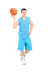 Full length portrait of a basketball player posing with a ball