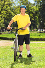 Mature man in sportswear posing next to his bike in a park
