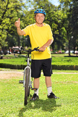 Man in sportswear giving thumb up next to his bike in a park