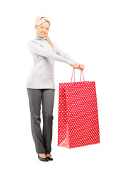 Full length portrait of a woman holding a big shopping bag