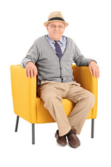 Senior sitting in a modern armchair and looking at camera