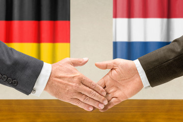 Vertreter Deutschlands und der Niederlande reichen sich die Hand