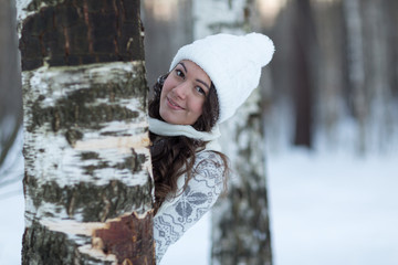 girl in white winter hat hiding behind a tree