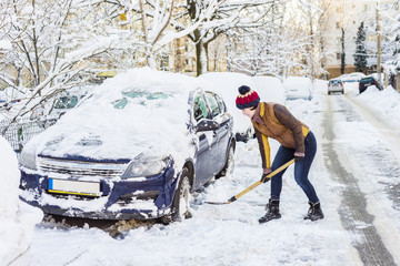 Beautiful young woman shoveling her car