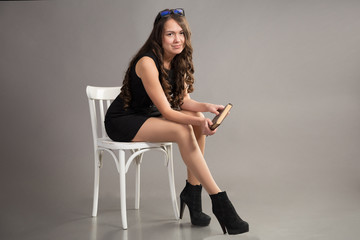 brunette with long hair in black dress sits on white chair