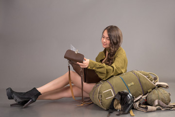 brunette in uniform of the Soviet army sits with bag board