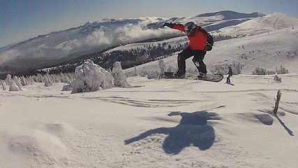 The snowboarder ride in the forest full of snow and jump