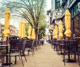 Tables, chairs and umbrellas set up for urban alfresco cafe restaurant sidewalk dining