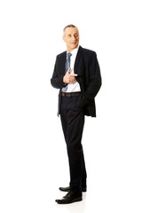 Full length businessman pointing to the right