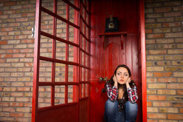 Troubled Woman Crouching in Red Telephone Booth