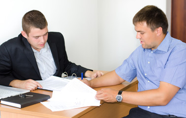 Two businessmen discussing a contract