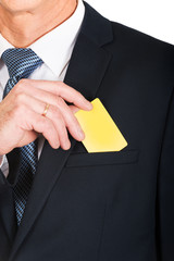 Businessman taking a yellow card from pocket