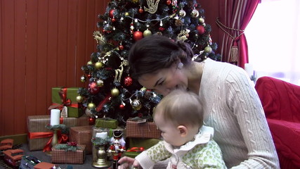 young mother with a child at Christmas tree where a lot of