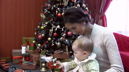young mother with a child at Christmas tree