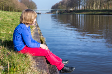 Young girl sitting at waterfront of canal