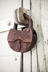 Big old rusted padlock hanging on rural door