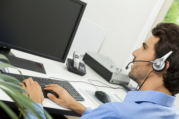 Man wearing headset giving online chat and support