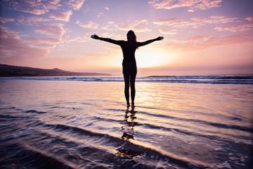 Junge Frau mit ausgestreckten Armen am Meer