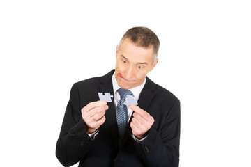 Businessman trying to connect puzzle pieces.