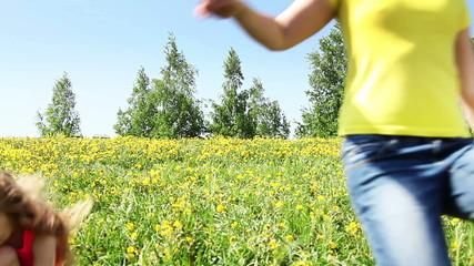 Large group of children run in dandelion field