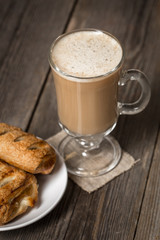 Coffee cup with fresh baked apple pies on wooden surface