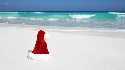Santa Hat on white sandy beach with Caribbean sea background