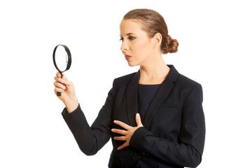 Smiling businesswoman with magnifying glass