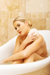 Woman relaxing in a bath and washing herself by sponge