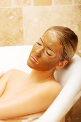 Woman relaxing in a bath with chocolate mask on her face