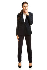 Full length shocked businesswoman covering mouth