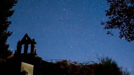Time lapse, campanario bajo las estrellas