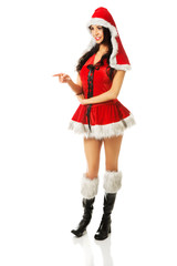 Woman wearing santa clothes pointing left