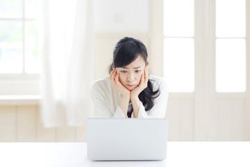 ノートパソコンを見て困る若い女性