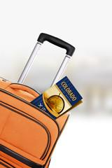 Colorado. Orange suitcase with guidebook.