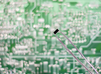 The chip in the tweezers on the circuit Board background