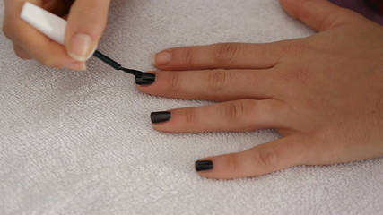 Woman polishing finger nails on white towel in beauty center