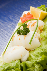 Squid with lettuce on blue glasstable