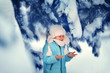 happy boy in the winter forest among the snowy pines playing and