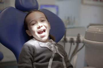 Niña con trenzas sonriendo en la consulta del dentista