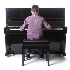 teenage boy sits at upright piano in studio