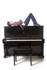 teenage boy lies upon upright piano in studio