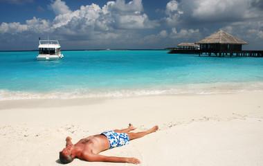 Man is relaxing on a maldivian beach