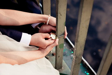 Newlyweds fix the lock on the bridge as a symbol of love