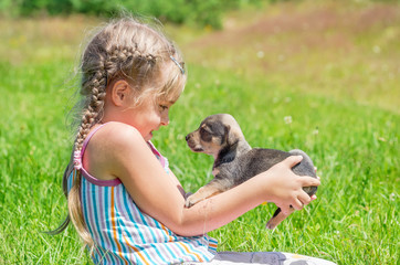 A child on a walk with a little puppy