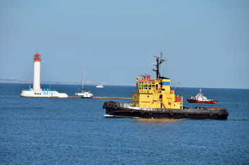 Tugboat in harbor quayside, over lighthouse in Odessa, Ukraine