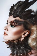 Portrait of young girl with feather make up and horn hairstyle