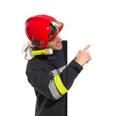 Smiling fireman in red helmet pointing at the blank banner