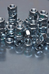 Group of steel nuts with green light reflection