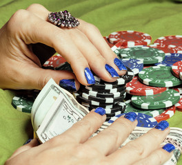 hands of young caucasian woman with blue manicure at casino