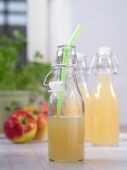 Apfelsaft in einer Flasche mit einem Strohhalm